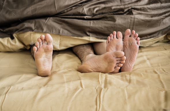 Caucasian couple lying on bed together - Stock Photo - Images
