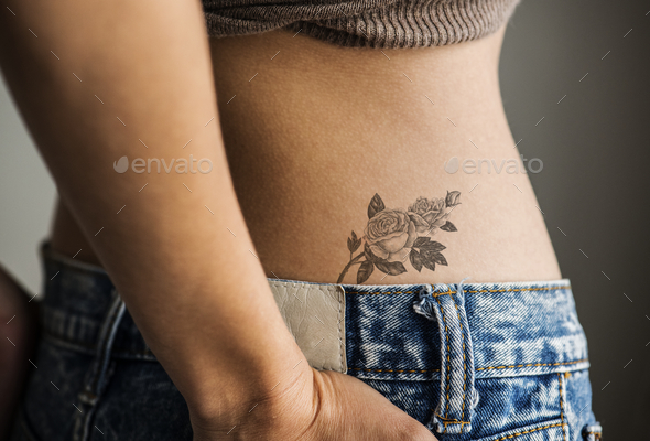 Closeup of lower hip tattoo of a woman - Stock Photo - Images