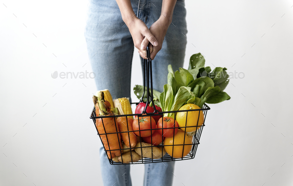 Woman holding a basket of vegetables - Stock Photo - Images
