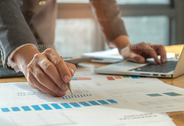 Businessman using pen pointing at graph and use the laptop. - Stock Photo - Images