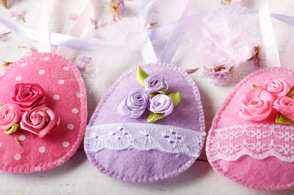 Handmade patchwork pink and lilac felt easter eggs on white wood - Stock Photo - Images