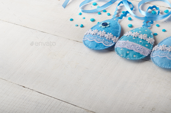 Handmade patchwork blue felt easter eggs on white wooden table - Stock Photo - Images
