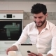 Man Uses Tablet in Kitchen - VideoHive Item for Sale