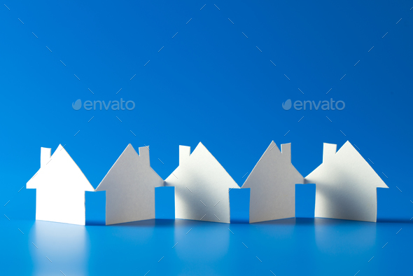 House cut out of paper on blue background - Stock Photo - Images
