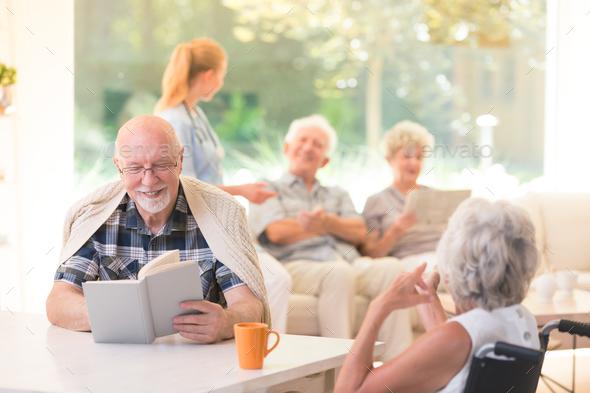 Smiling senior man reading book - Stock Photo - Images