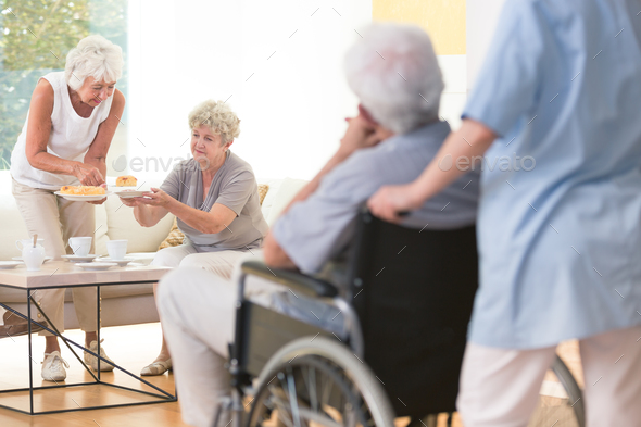 Senior woman giving cake - Stock Photo - Images