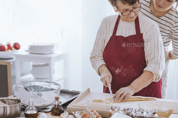 Grandmother concentrating on cutting dough - Stock Photo - Images