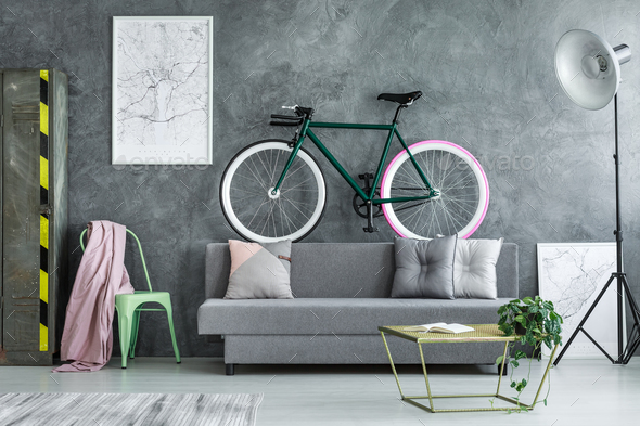 Black bike on grey sofa - Stock Photo - Images