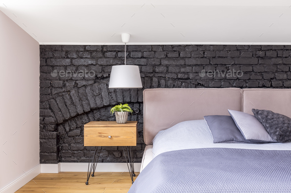 Bed against black brick wall - Stock Photo - Images