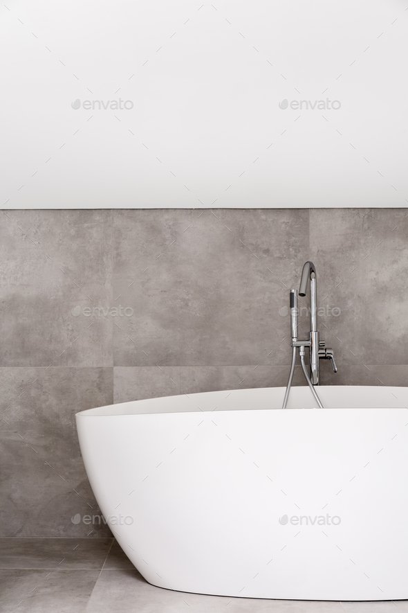 Oval bathtub in empty bathroom - Stock Photo - Images