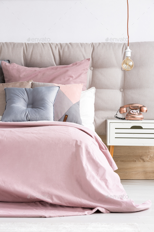 Bed with soft pink coverlet - Stock Photo - Images