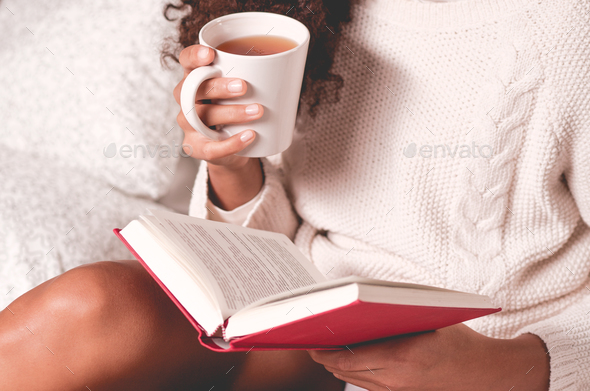 Hands holding book and mug - Stock Photo - Images