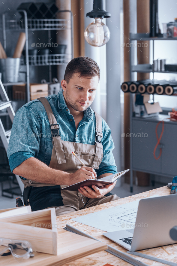 Young carpenter working using laptop - Stock Photo - Images