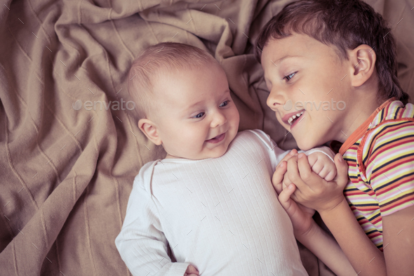 little boy playing with newborn on the bed - Stock Photo - Images