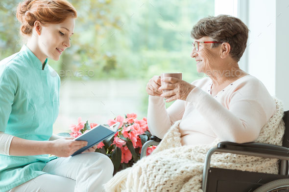 Assistant reading book to elder - Stock Photo - Images