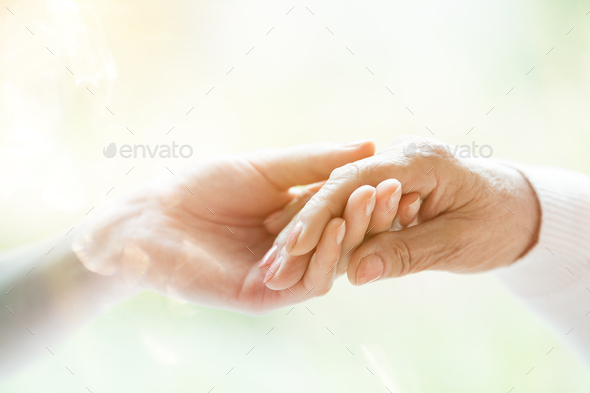 Young hand holding elderly hand - Stock Photo - Images