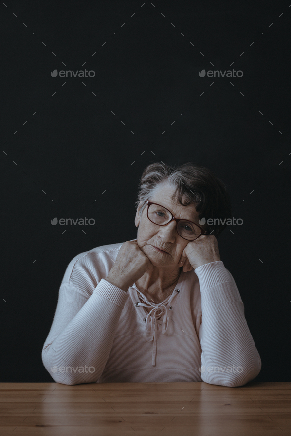 Grandmother sitting alone at table - Stock Photo - Images