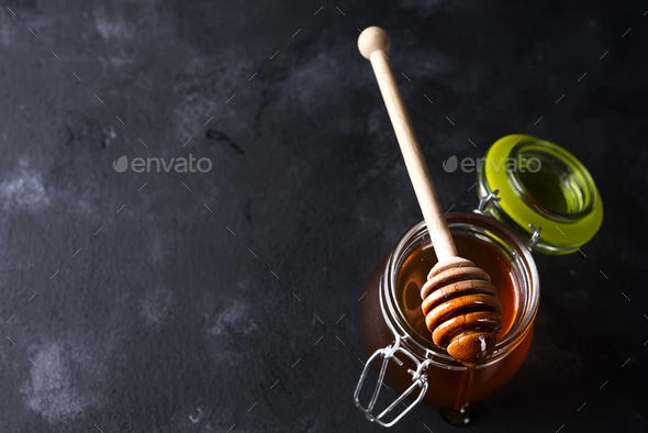 Spoon of honey with jar On a black background - Stock Photo - Images
