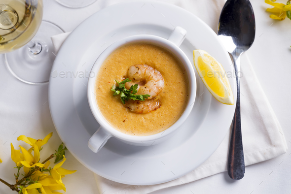 Creamy soup with seafood and lemon on a white background. - Stock Photo - Images