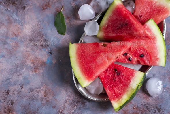 slices of watermelon on a iron plate with ice - Stock Photo - Images