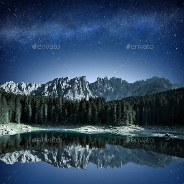 mountain range and fir forest reflecting in alpine lake at night - Stock Photo - Images