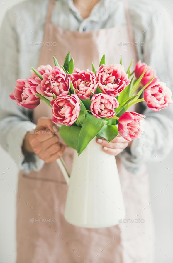 Woman holding white enamel vase with fresh pink tulips - Stock Photo - Images