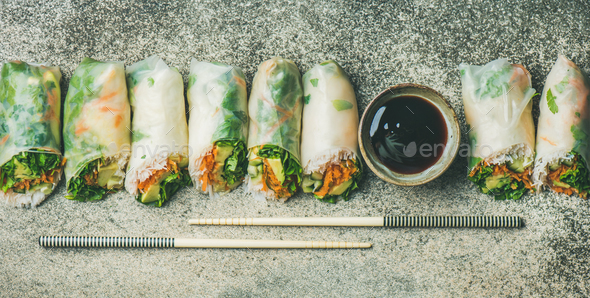 Vegan spring rice paper rolls over concrete background, wide composition - Stock Photo - Images
