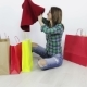 A Happy Young Woman Taking Out New Clothes From Colored Bags Sitting on the Floor at Home. - VideoHive Item for Sale