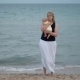 Mother with Lost Look Holding Baby Being Alone at the Beach Near Sea - VideoHive Item for Sale