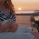 Mother Nursing and Caressing Baby Sitting on the Pier at Sunset - VideoHive Item for Sale