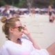 A Thoughtful, Sad Woman Sits Alone on the Sand in a Crowded Beach - VideoHive Item for Sale