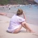 A Thoughtful, Sad Woman, Sits Alone on the Sand in a Crowded Beach, , . Background Blur - VideoHive Item for Sale