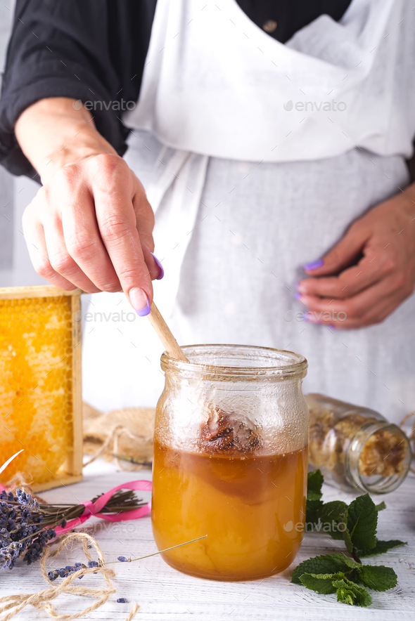 Hand with dipper picking honey from a jar of honey. - Stock Photo - Images