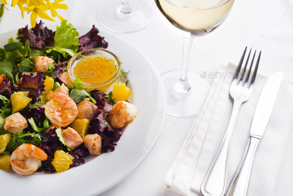 Tropical salad with prawns, lettuce, oranges and mango served on a plate with orange mustard sauce - Stock Photo - Images
