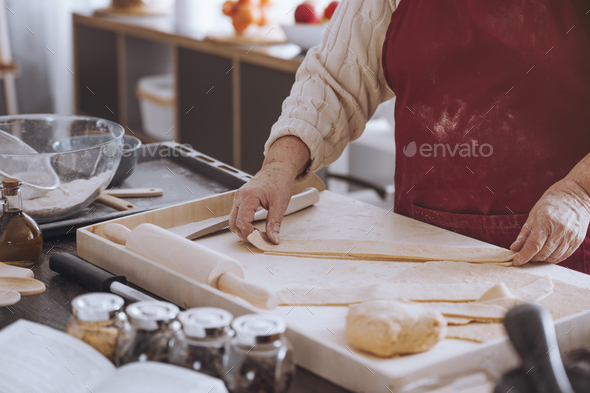 Person cutting dough into strips - Stock Photo - Images