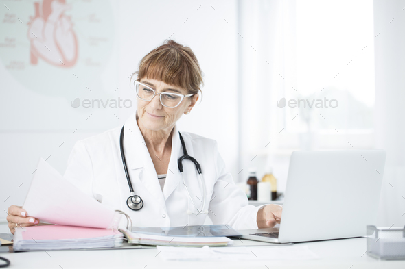 Smiling cardiologist working in office - Stock Photo - Images