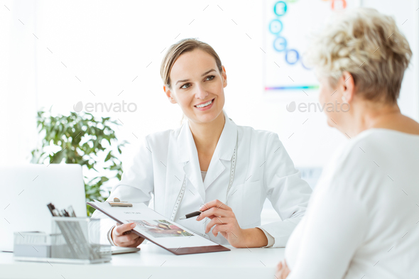 Smiling nutritionist showing healthy diet - Stock Photo - Images
