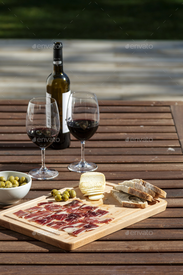 outdoor table setting with red wine cheese and bread - Stock Photo - Images