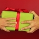 Young Man Gives a Gift on Red Background. Green Gift Box with Red Ribbon Opening. Congratulate Happy - VideoHive Item for Sale