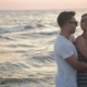 Portrait of Hansome Boyfriend Hugging His Blonde Girlfriend Standing Near the Sea During Sunset - VideoHive Item for Sale