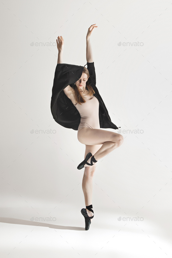 Young beautiful dancer in beige swimsuit dancing on gray background - Stock Photo - Images