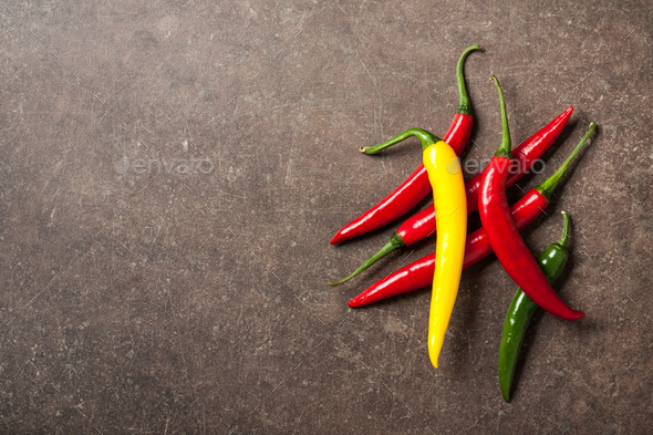 Colorful chili peppers on stone background - Stock Photo - Images