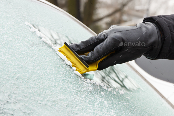 Hand in leather glove scraping ice or snow from window of car - Stock Photo - Images