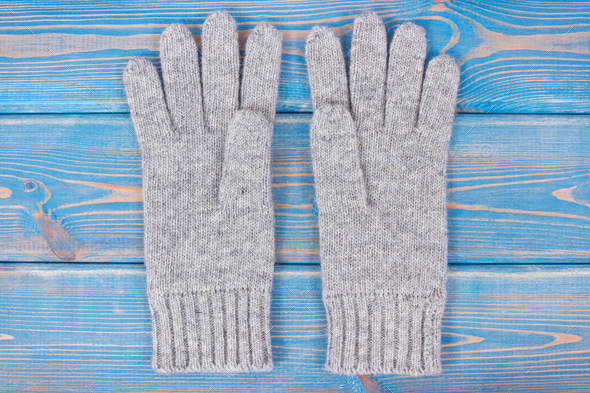 Pair of woolen gloves for woman on old blue boards - Stock Photo - Images