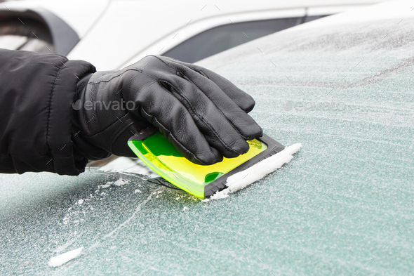 Hand of man in leather glove scraping ice from car windscreen - Stock Photo - Images