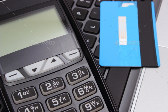 Payment terminal and credit card on laptop keyboard - Stock Photo - Images