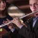 A Guy in a Jacket and Shirt Plays the Flute, and a Beautiful Brunette in a Blue Dress Playing a - VideoHive Item for Sale