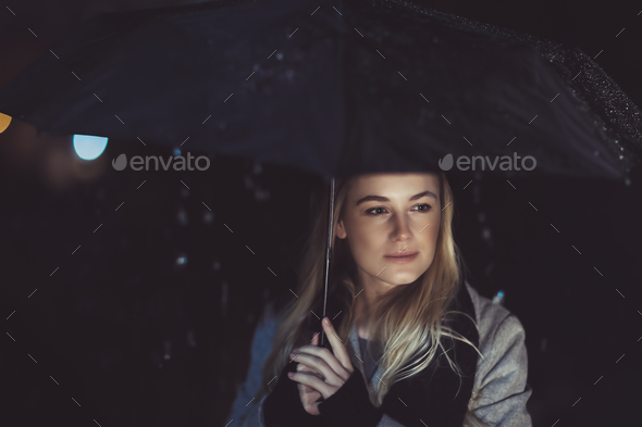 Thoughtful woman outdoors on rainy night - Stock Photo - Images