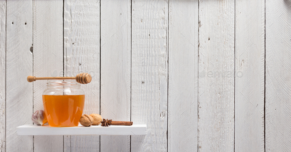 glass jar of honey on wooden shelf - Stock Photo - Images