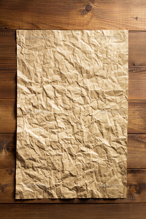 wrinkled paper at wooden plank - Stock Photo - Images